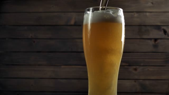Beer poured in glass on wood background. Foam sliding down side. Slow motion Beer poured in glass on wood background. Foam sliding down side lager stock videos & royalty-free footage