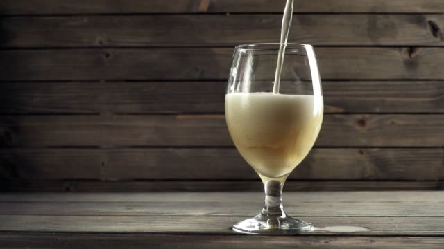 Beer poured in glass on wood background. Slow motion Beer poured in glass on wood background. Slow motion lager stock videos & royalty-free footage