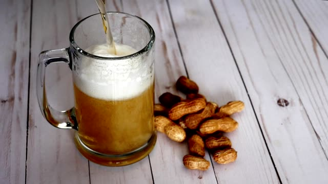Beer pouring into mug and peanuts