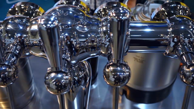 Beer rack with chrome-plated faucets for pouring a foamy drink shine in a light Beer rack with chrome-plated faucets for pouring a foamy drink shine in the light. Shot in motion handle stock videos & royalty-free footage