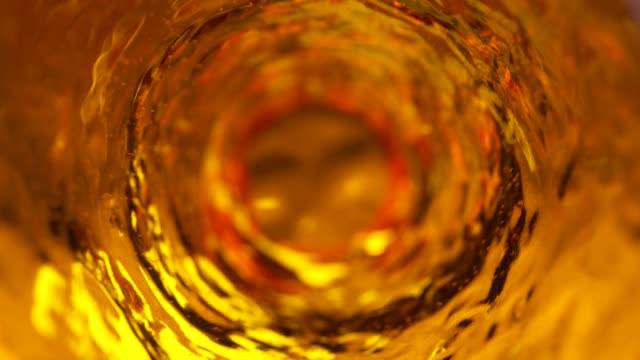 la birra con bolle si muove in un bicchiere al rallentatore. sfondo astratto dell'acqua. rendering 3d ad anello senza soluzione di continuità - whisky video stock e b–roll