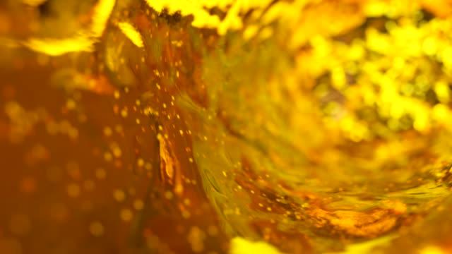 vídeos de stock, filmes e b-roll de cerveja com bolhas se move em um copo em câmera lenta. fundo de água abstrata. renderização de loop 3d sem emenda - tea drinks