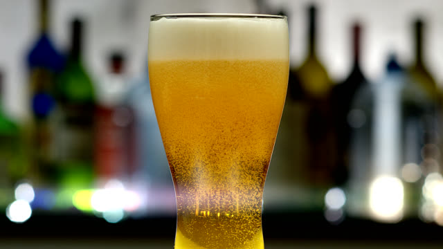 Beer-4K Beer poured in a pilsner glass in a bar setting. Shot in 4K. lager stock videos & royalty-free footage