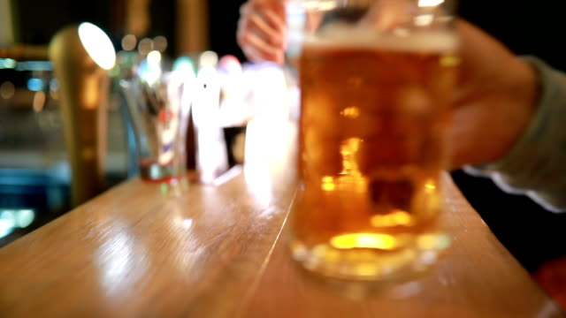 Beers and cheers Video of unrecognizable people raising mugs of beer in the bar,close up bar counter stock videos & royalty-free footage