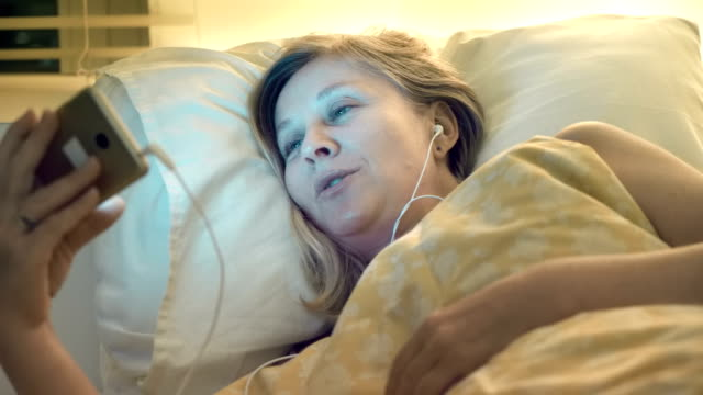 Before falling asleep a woman wishes a good night to a loved one via the Internet using a smartphone video