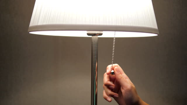Before Sleeping Night, Female Hand Pulls Lamp Switch Circuit And Turns Off Light