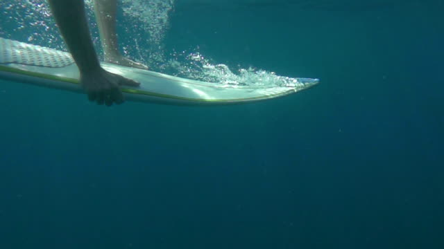 SLOW MOTION UNDERWATER: Beginner surfer duck diving board under oncoming wave video