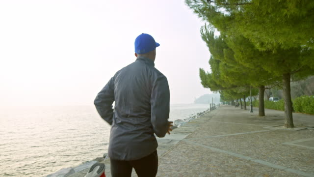 SLO MO TS Behind a male runner running on a wide footpath along the sea