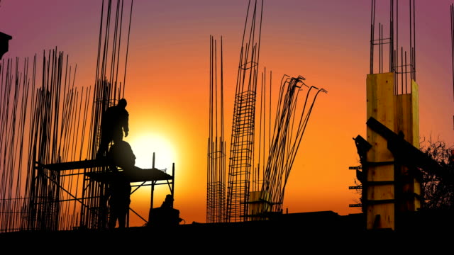 behind a metal frame workers secure poles with wire to the base of a reinforced concrete pillar on a construction site at sunset - spranga video stock e b–roll