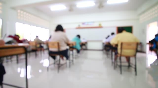 dietro ragazze gruppo studenti universitari test di esame in camera e studente seduto su sedia a remi facendo esami finali in classe con uniforme thailandia. concetto di educazione asiatica. vista dall'alto. - esame università video stock e b–roll