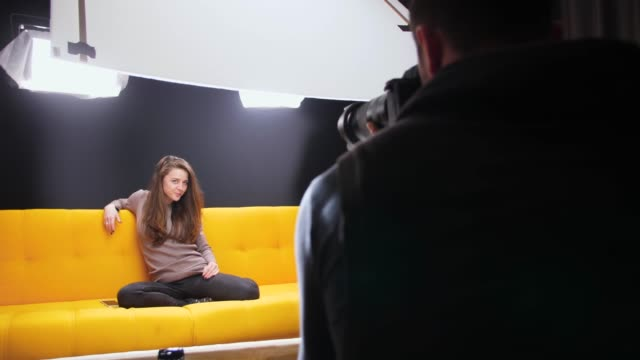 Behind the scenes on a photo shoot Behind the scenes on a photo shoot. The woman is of caucasian ethnicity and is casually dressed. The scene is situated in a studio environment in front of black background. Location of the shoot is Sofia, Bulgaria (Eastern Europe). The footage is shot on Panasonic GH5 camera. photo shoot stock videos & royalty-free footage