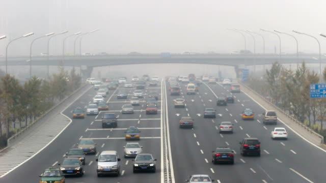 vídeos de stock e filmes b-roll de pequim, china-out 25, 2014: o mau tempo, as pessoas conduzir cuidadosamente na estrada, pequim, china - neblina causada por temperatura elevada