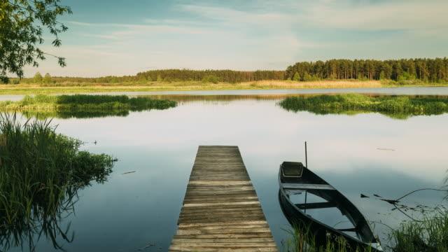 beyaz rusya, göl veya nehir ve eski ahşap kürek balıkçı teknesi eski ahşap i̇skele yakın güzel yaz güneşli akşam - full hd format stok videoları ve detay görüntü çekimi