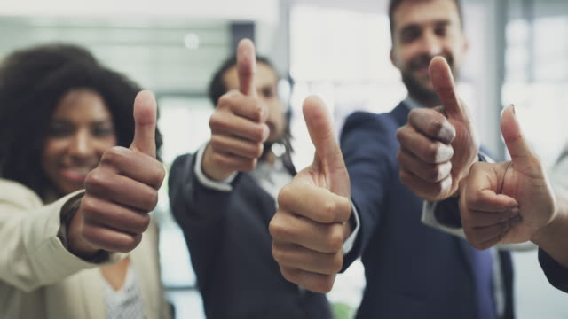 Believe in yourself, because we do! 4k video footage of a group of businesspeople showing thumbs up together in an office representing stock videos & royalty-free footage
