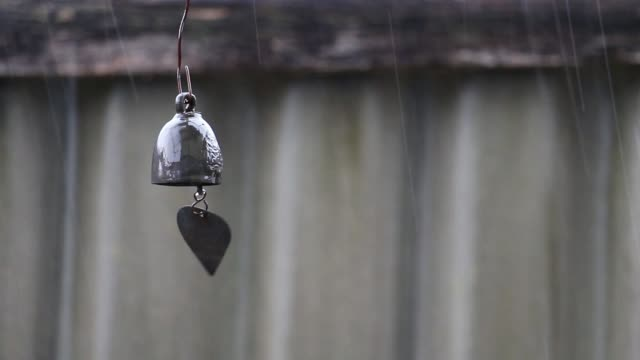 Bell or chime hanging and swaying in wind that is in the rain.