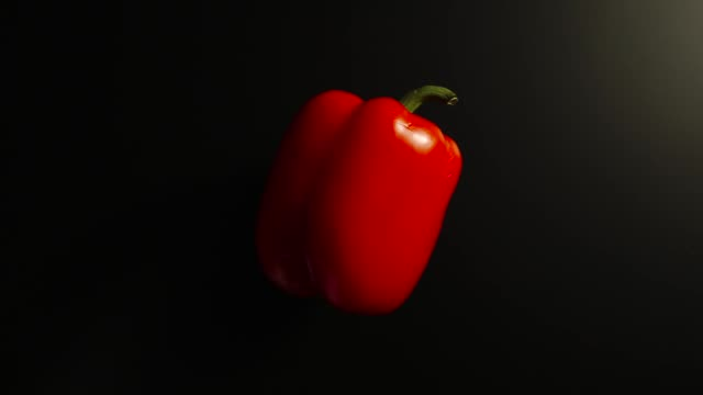 vídeos de stock e filmes b-roll de top view: bell pepper on a side rotates on a black surface - stop motion - red bell pepper isolated