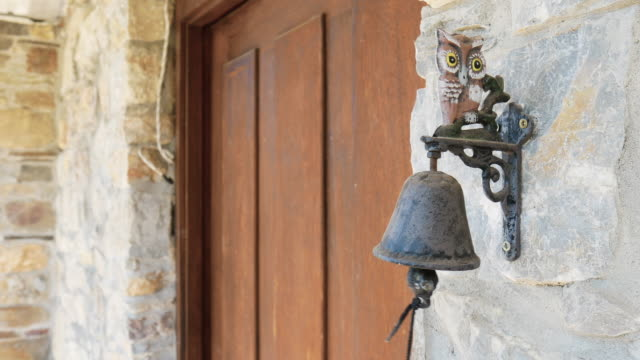 Bell ringing at the entrance of a rural stone house
