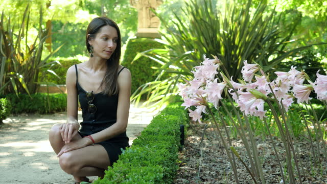Belladonna lily. Beautiful young caucasian woman sitting by flowering plant of Amaryllis Belladonna in Botanical garden on sunny summer day. Madrid. Spain. 4K