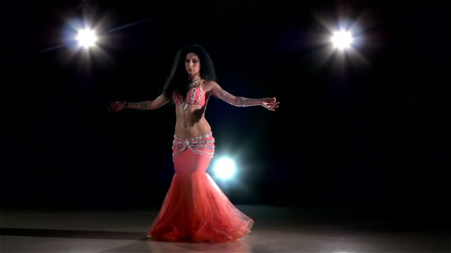 Belly dance of sexy woman in shiny pink dress, on black, back light, slow motion video