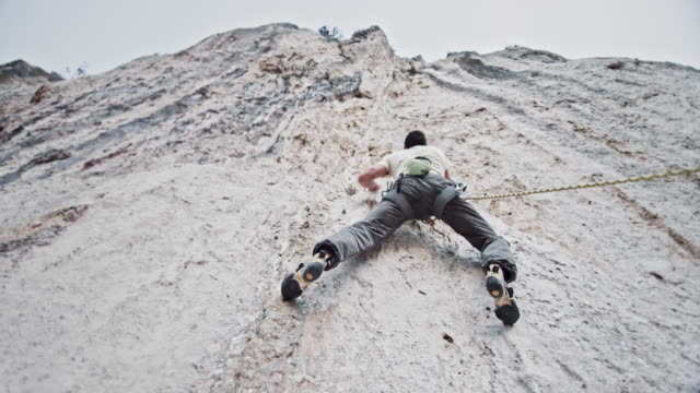 Below a male rock climber ascending a vertical white cliff Medium low angle handheld shot of a man rock climbing up a white cliff. Shot in Croatia. conquering adversity stock videos & royalty-free footage