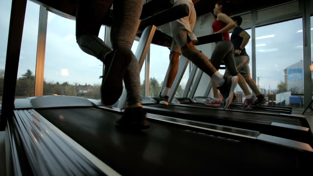 below view of athletic people jogging on treadmills in a gym. slow motion. - praticare video stock e b–roll
