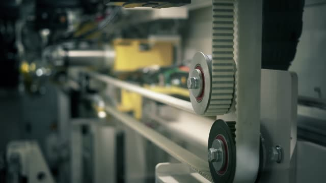 belt machine operating in a factory. automated equipment needed in industry and engineering process - close-up - azionare video stock e b–roll