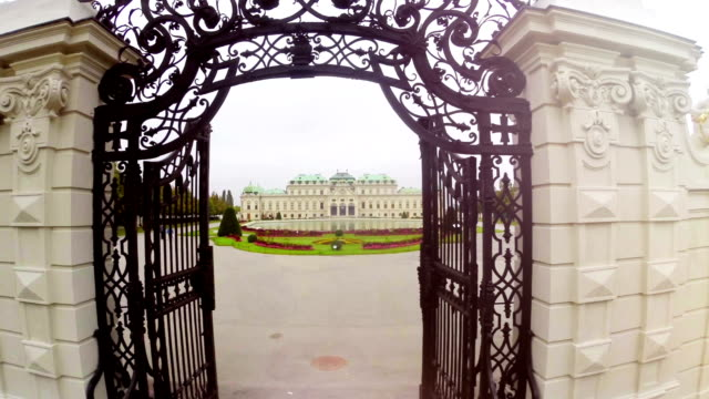 Belvedere Palace aerial fly through gates, famous tourist attraction, Austria capital sight seeing, royal Belvedere residence, marble lions and drums, garden and pond  fly over, travel tour place video