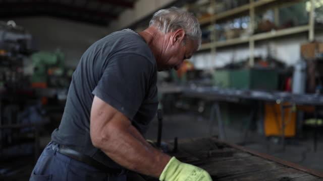 Bending metal with hands Senior man bending metal parts for metal fence, working with hands without tool steel mill stock videos & royalty-free footage