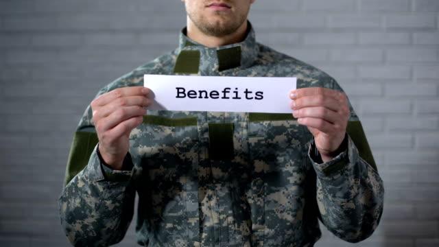 benefici parola scritta sul segno nelle mani di soldato maschio, sostegno veterani, aiuto - indennità video stock e b–roll