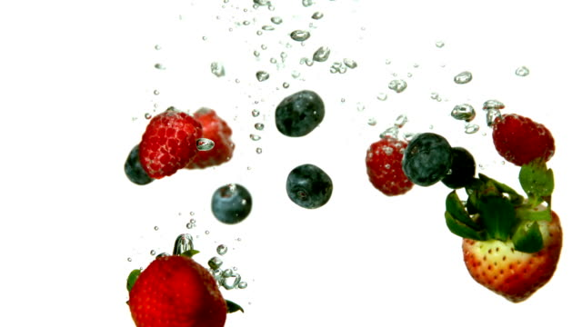 Berries falling in water on white background video