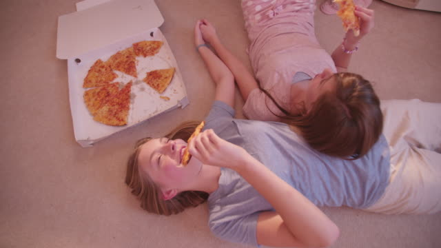 besten freunde liegend dem boden essen pizza hände halten - teenage friends sharing food stock-videos und b-roll-filmmaterial