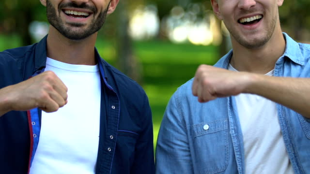 Best male friends smiling to camera making fist-bump, real friendship, close-up