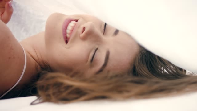 Between the sheets. Smiling woman flirting with camera