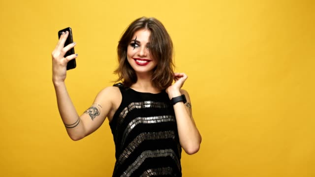 Beutiful happy woman with creepy halloween make up making selfie on smartphone isolated over yellow video
