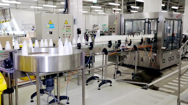 Beverage industry manufacturing line. Milk bottles on conveyor belt video