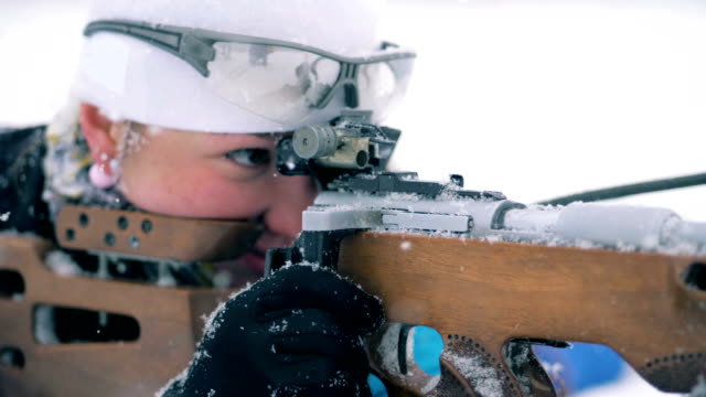 Biathlon riffle is getting reloaded by a sportswoman while lying