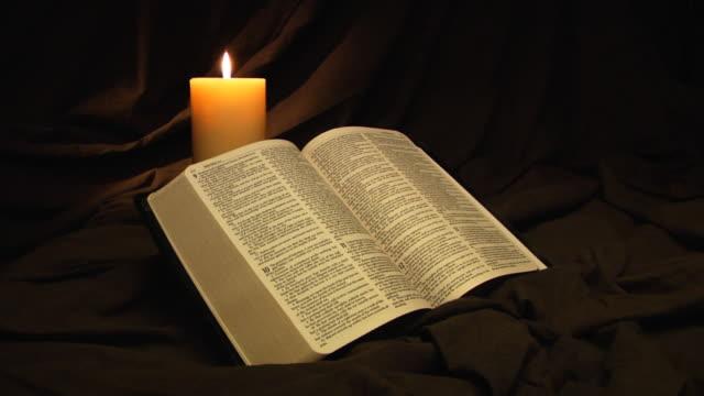 stockvideo's en b-roll-footage met bible and candle - heilig geschrift