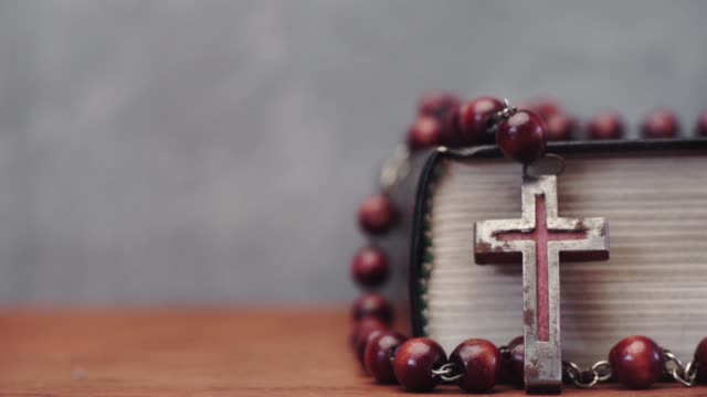Bible and the crucifix beads on a red wooden table. Beautiful background. Religion concept close up