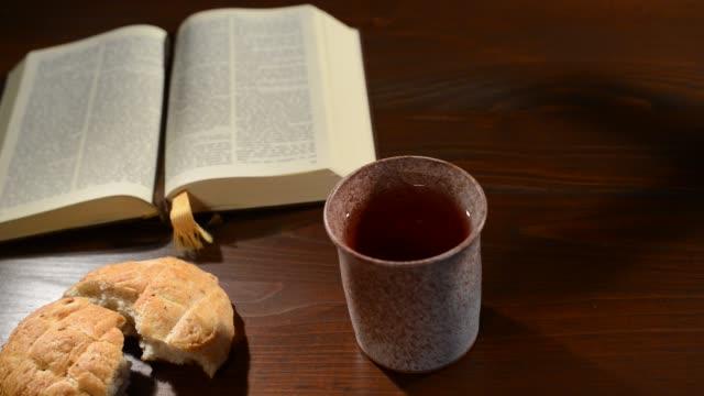 vídeos de stock, filmes e b-roll de bíblia com cálice e pão. visão panorâmica - primeira comunhão