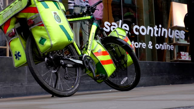 Bicycle ambulance Manchester city centre center shopping street scene, England, UK.People passing NHS Cycle Response Unit bicycle loaded with first aid equipment in a busy pedestrian area nhs stock videos & royalty-free footage