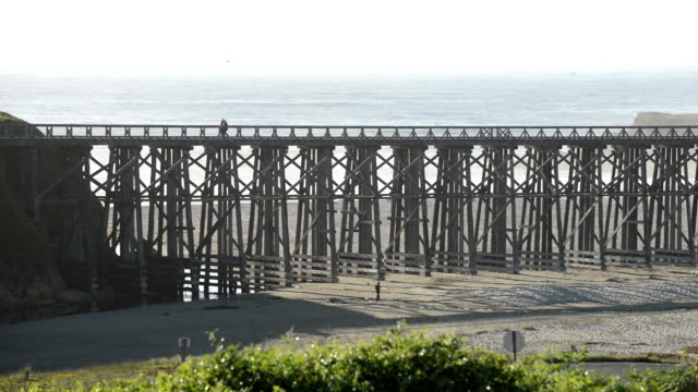 Bicycle crosses foot bridge by the ocean shore, time lapse