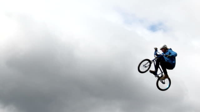 BMX bicycle man jumps high cloudy background slow motion video