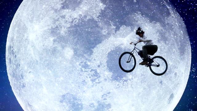 Bicycle moon flyer, male bike across night sky slow motion video