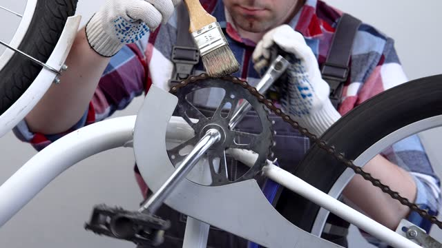 Bicycle preparation. A male repairman lubricates a bicycle chain with a brush.