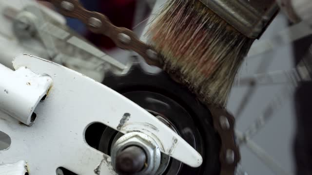 Bicycle preparation. Repairman lubricates a bicycle chain with a brush, close-up
