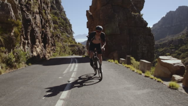 bicycle rider riding up the mountain - ciclismo su strada video stock e b–roll