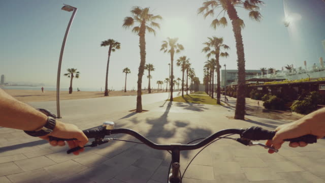 POV bicycle riding in Barceloneta beach during summer vacations video