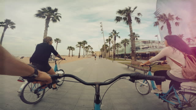 pov bicycle riding with friends at barceloneta beach in barcelona, spain - turystyka filmów i materiałów b-roll