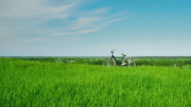 自転車は、緑の草原、青い空を背景に立っています。idylistic 風景、カメラをスムーズに自転車に移動します。 - 田舎のライフスタイル点の映像素材/bロール