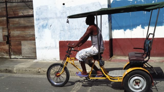 Bicycle taxi driver with his vehicle, Cuba video